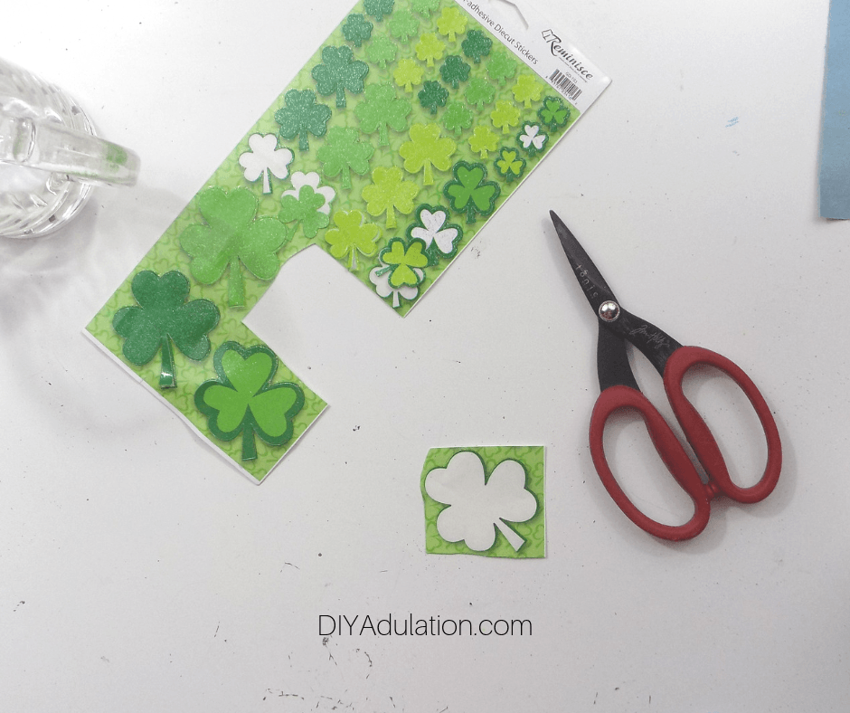Shamrock Sticker Negative Cut Out of Sticker Sheet next to Scissors