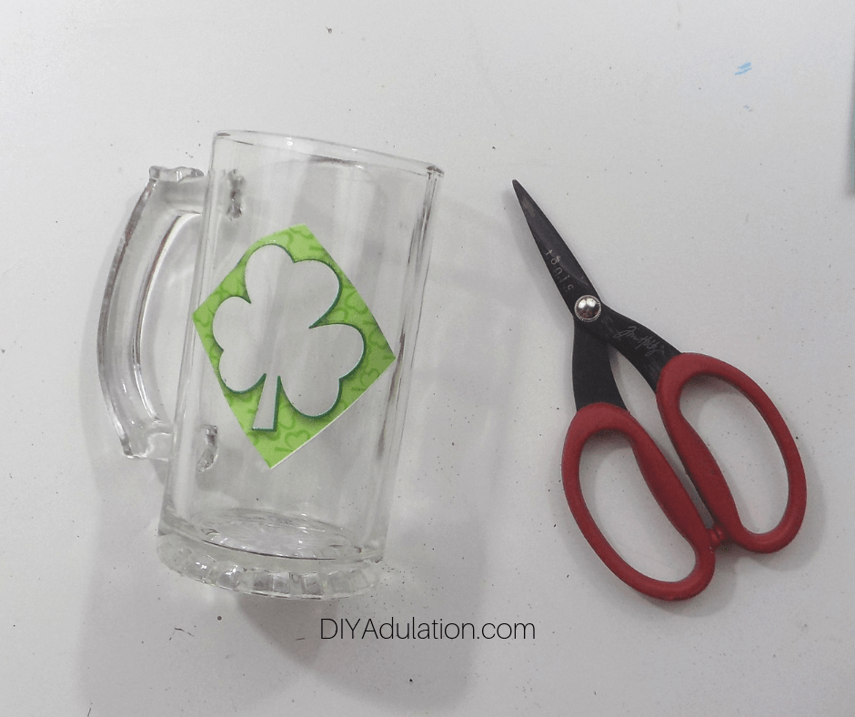 Shamrock Sticker Negative on Clear Glass Stein next to Scissors