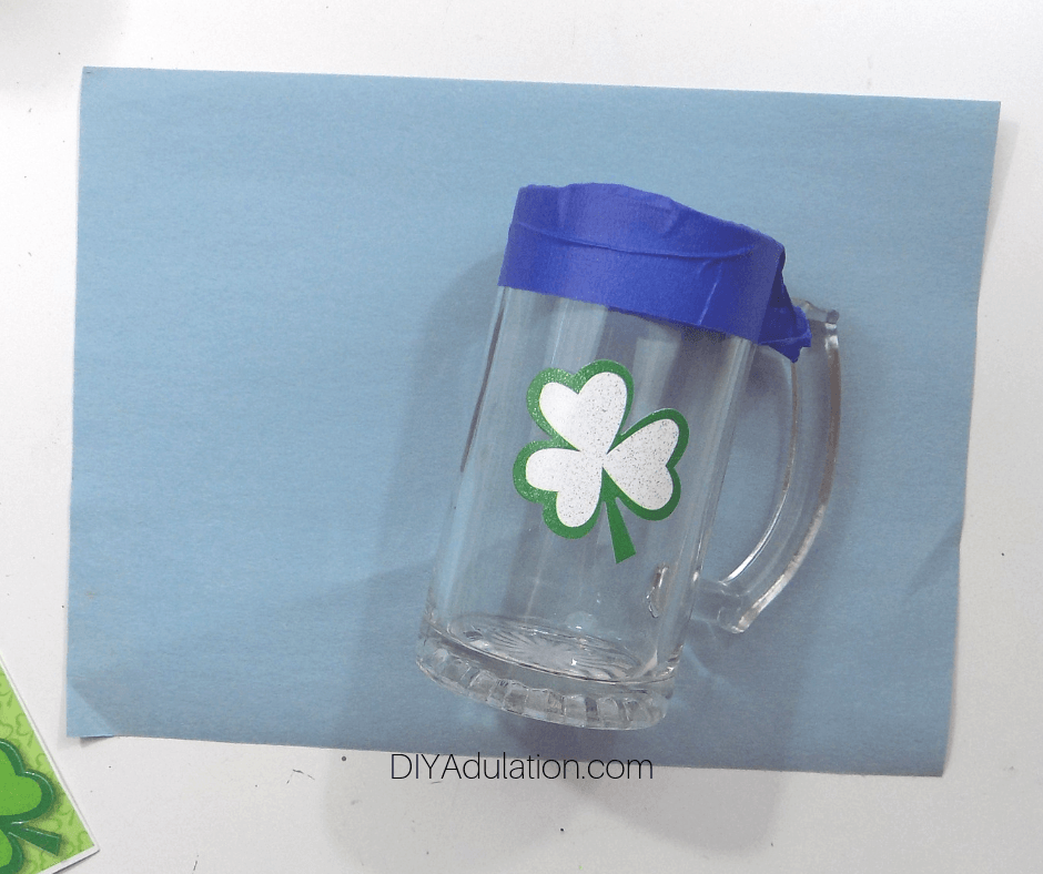 Shamrock Sticker and Blue Painters Tape on Clear Glass Stein