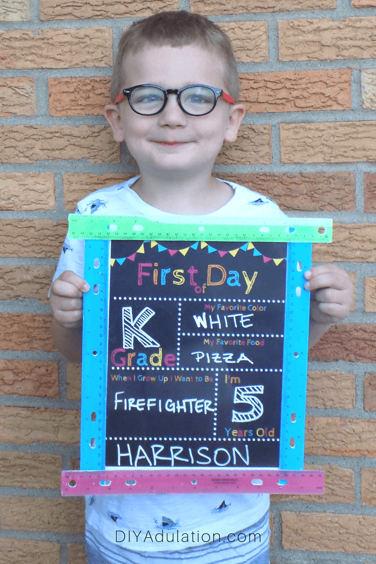 Smiling Boy Holding First Day of School Sign