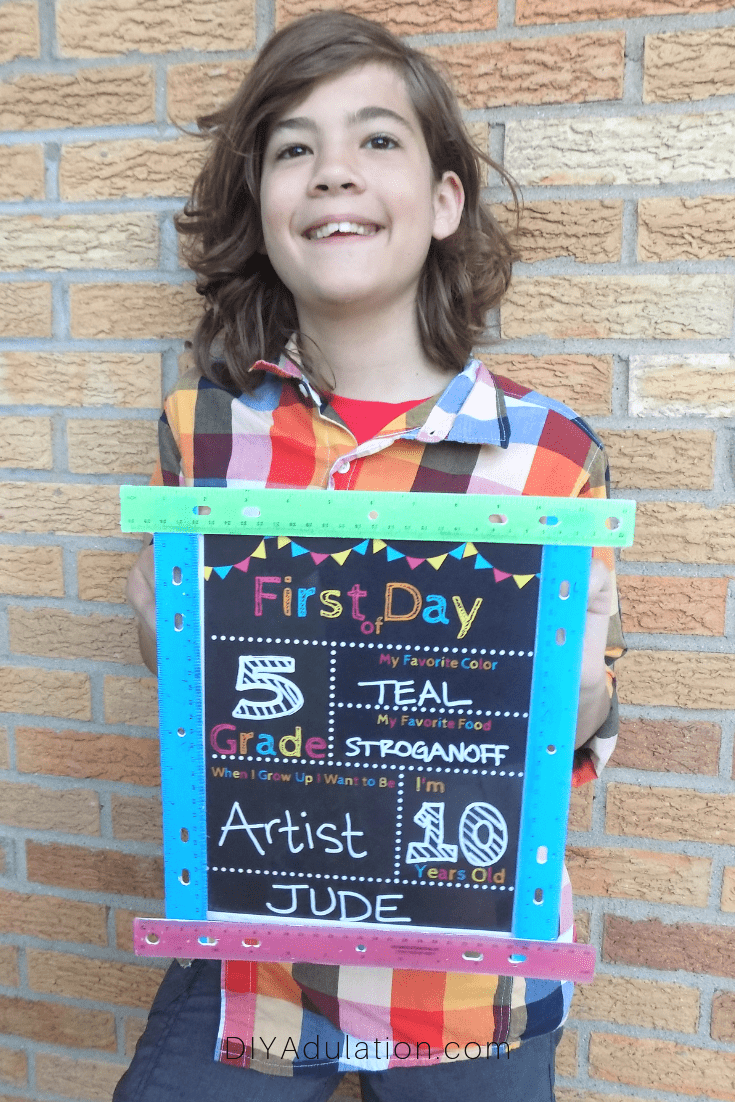 Smiling Child Holding First Day of School Sign