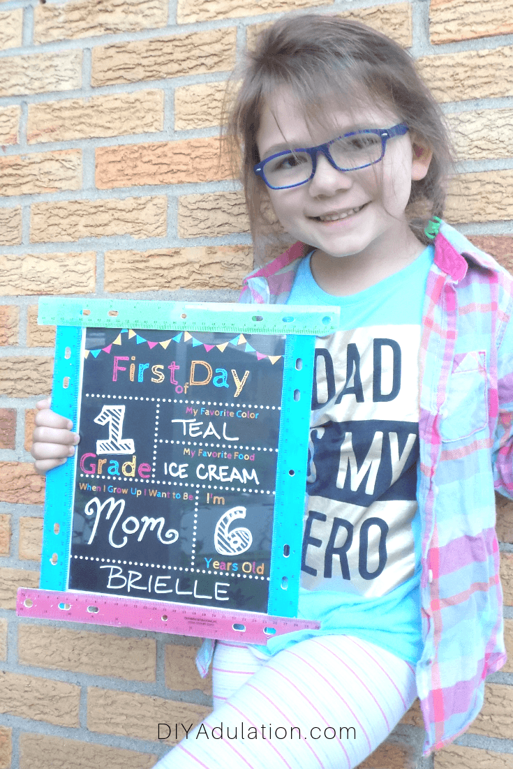 Smiling Girl Holding First Day of School Sign