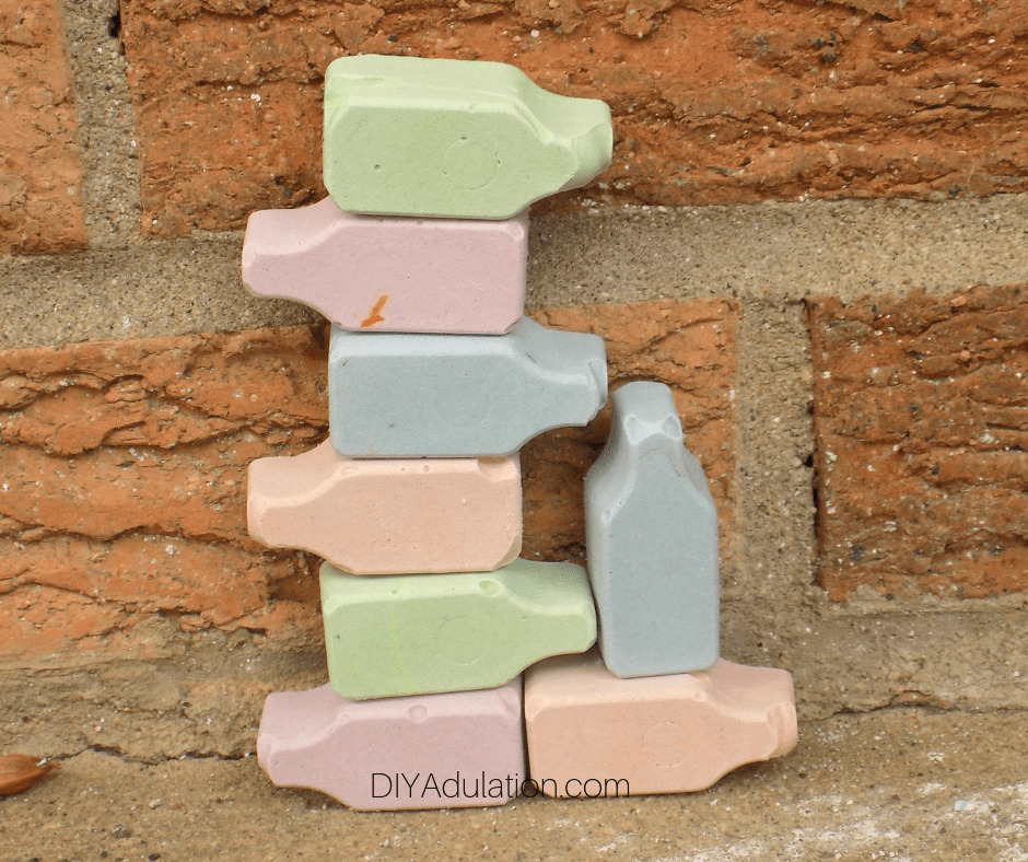 Stacked Sidewalk Chalk in Front of Brick Background
