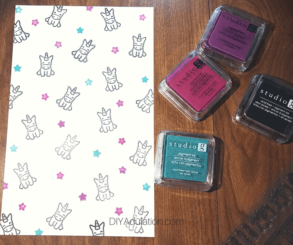 Stamped Stars and Unicorns on White Paper Next to Ink Pads and Stamp Set