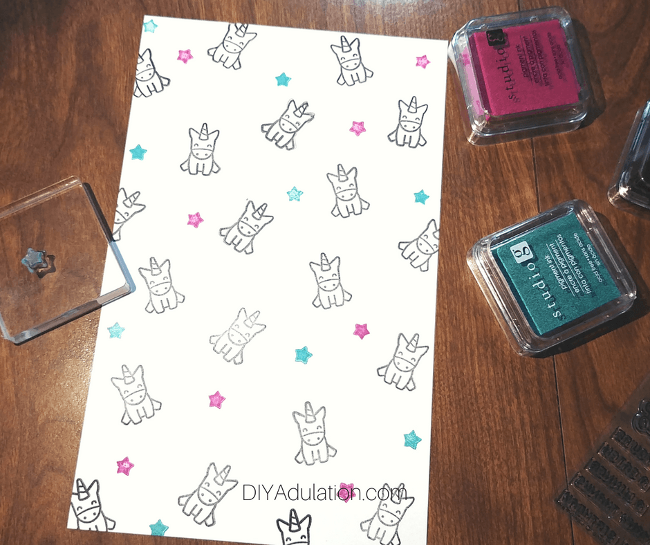 Stamped Stars and Unicorns on White Paper Next to Ink Pads and Stamps