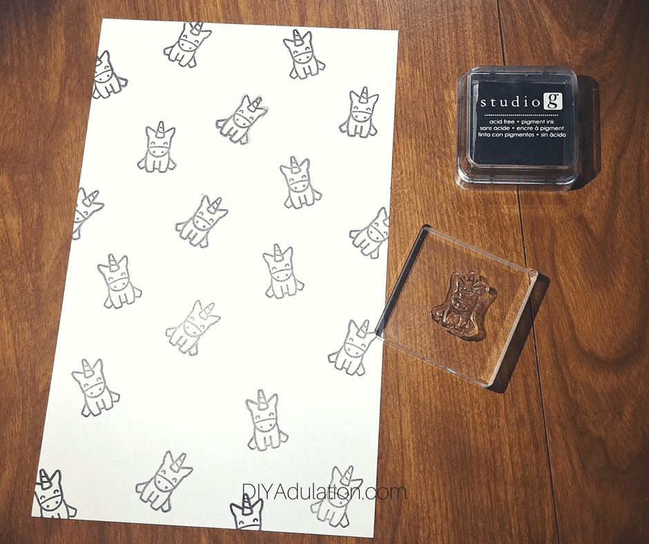 Stamped Unicorns on White Paper Next to Ink Pad and Stamp