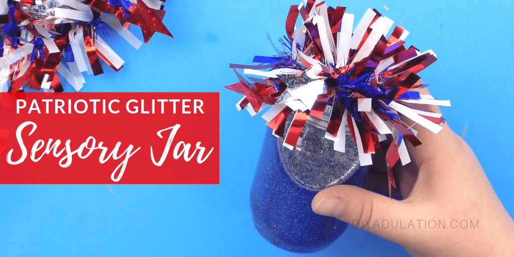 Hand Holding Patriotic Glitter Sensory Jar with Garland on Lid with text overlay - Patriotic Glitter Sensory Jar