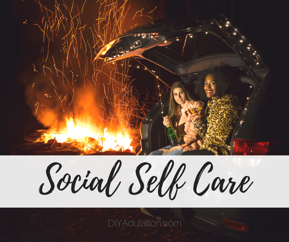 Two women in back of SUV next to bon fire with text overlay - Social Self Care