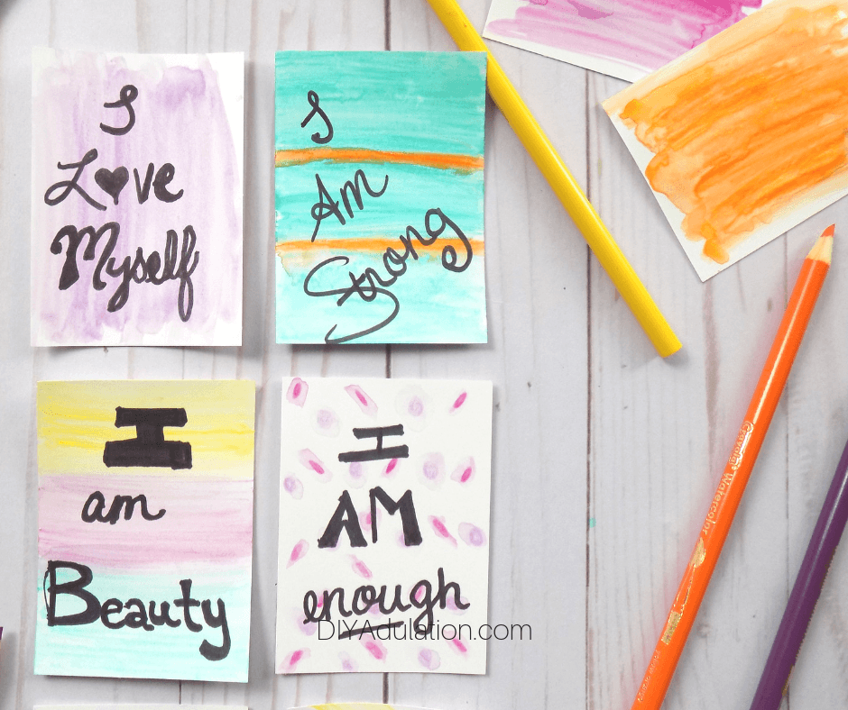 Watercolor Affirmation Cards next to Color Pencils and Watercolor Cards