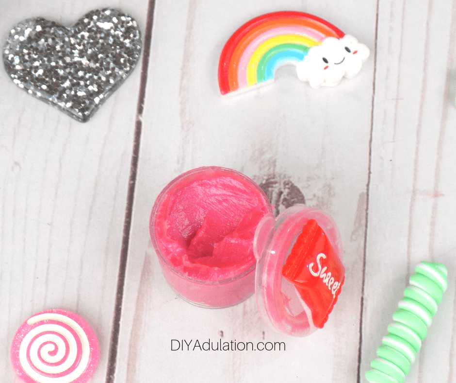 Watermelon Lip Gloss Next to Decorative Lid