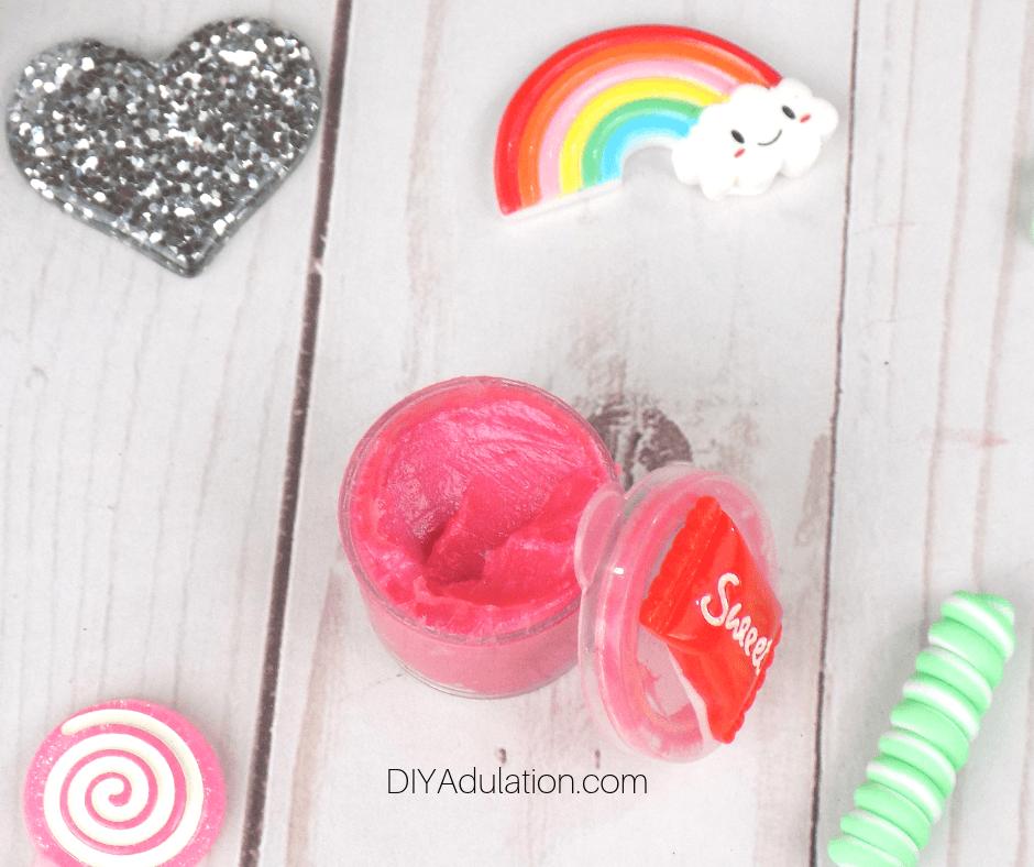 Watermelon Lip Gloss Next to Decorative Lid