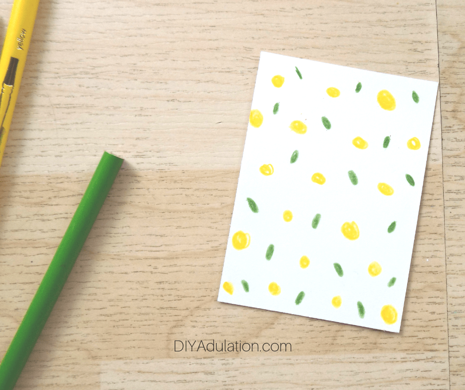 Yellow and Green Dot Card next to Colored Pencils