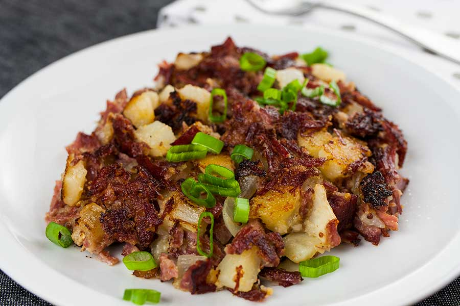 Plate of corned beef hash topped with scallions