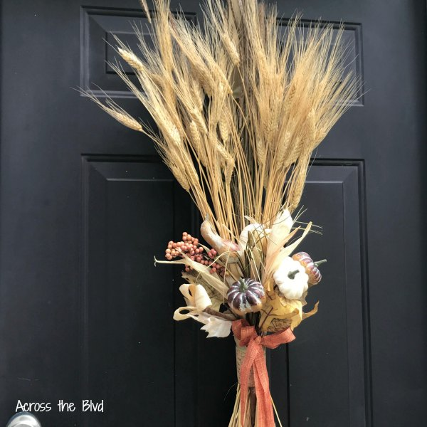 Sheaf of wheat with ribbons and gourds on a black door