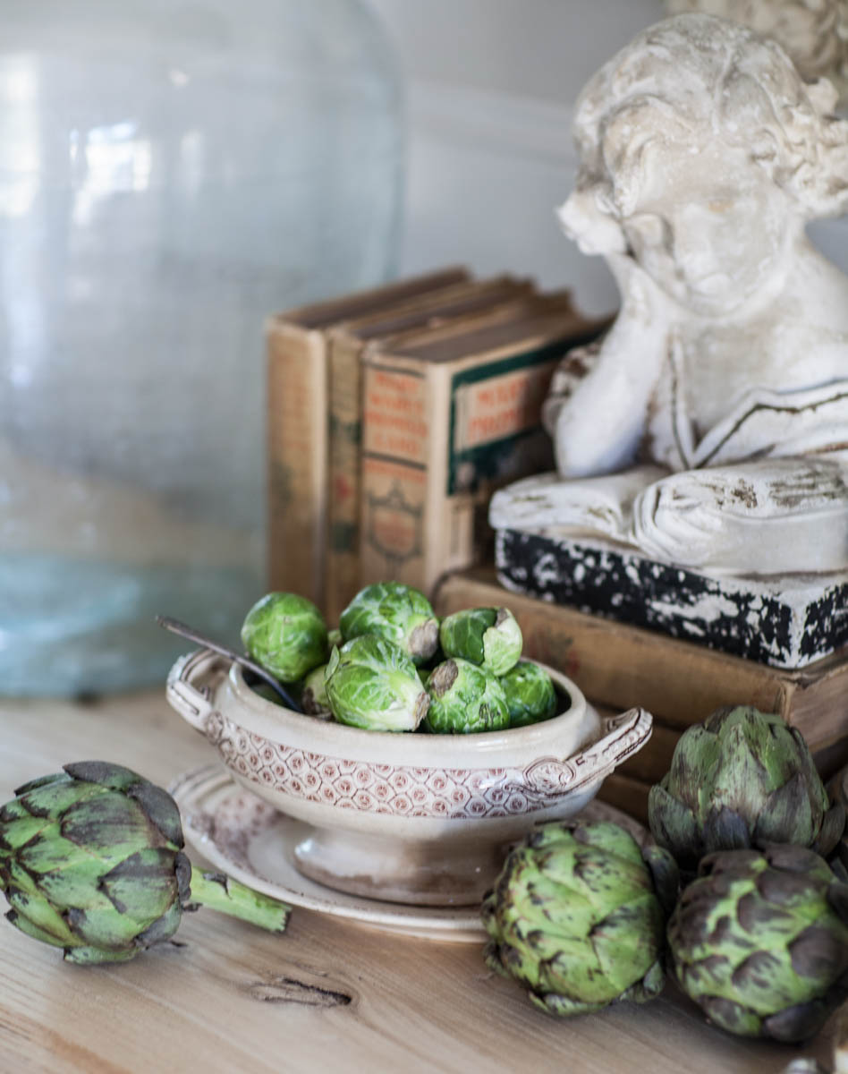 Bowl of brussel sprouts next to books and artichokes