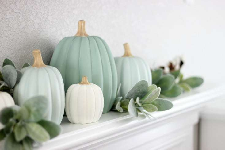 Teal and cream pumpkins on a mantle