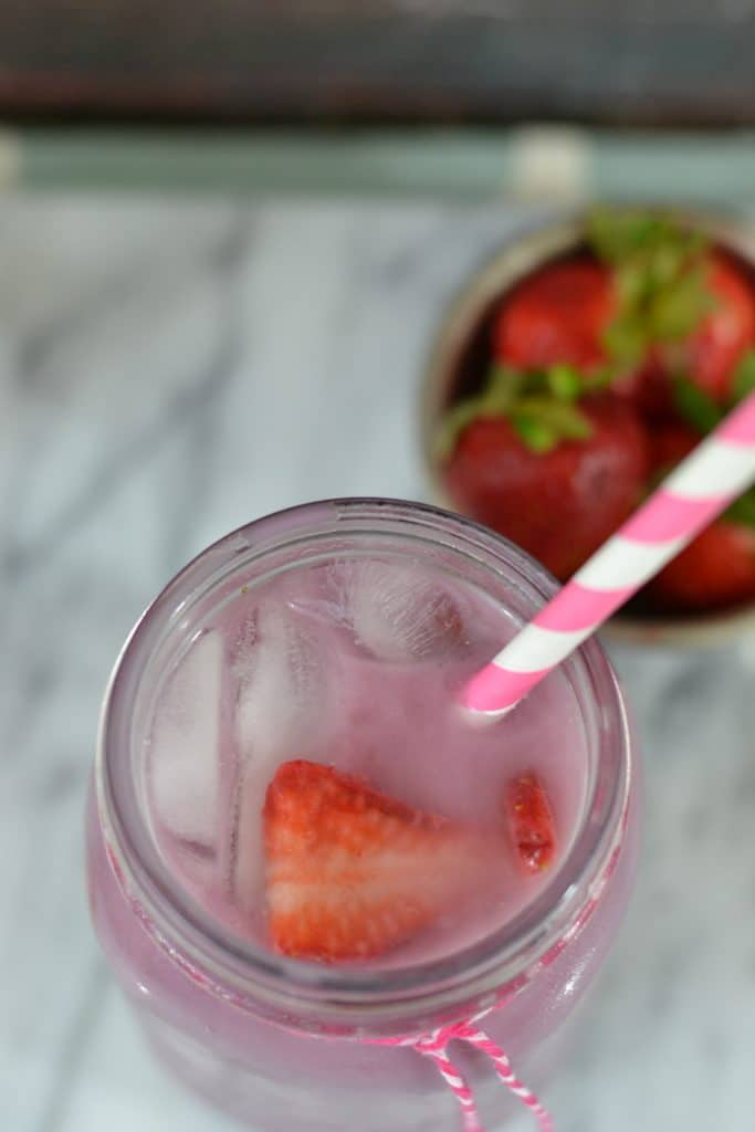 Overhead photo of pink drink with strawberries