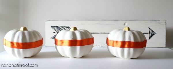 white pumpkins with orange ribbon wrapped around them