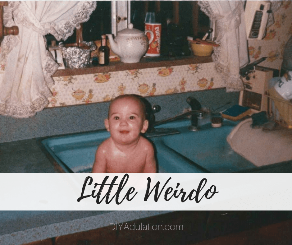 Baby in kitchen sink with text overlay - Little Weirdo