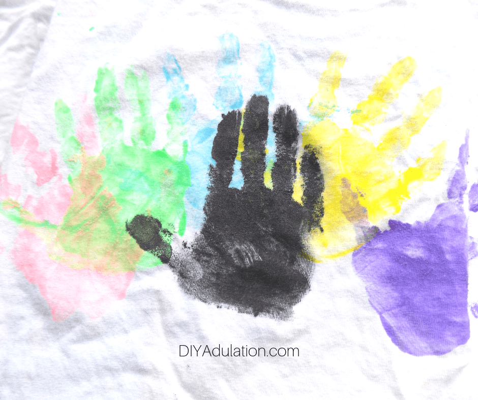 Black Hand Print over Colorful Hand Prints on White T-Shirt