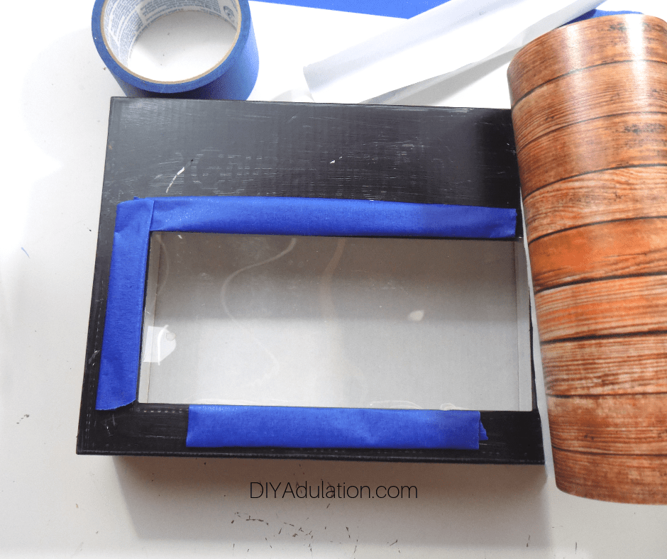 Blue Painters Tape Attached to Edge Window in Box