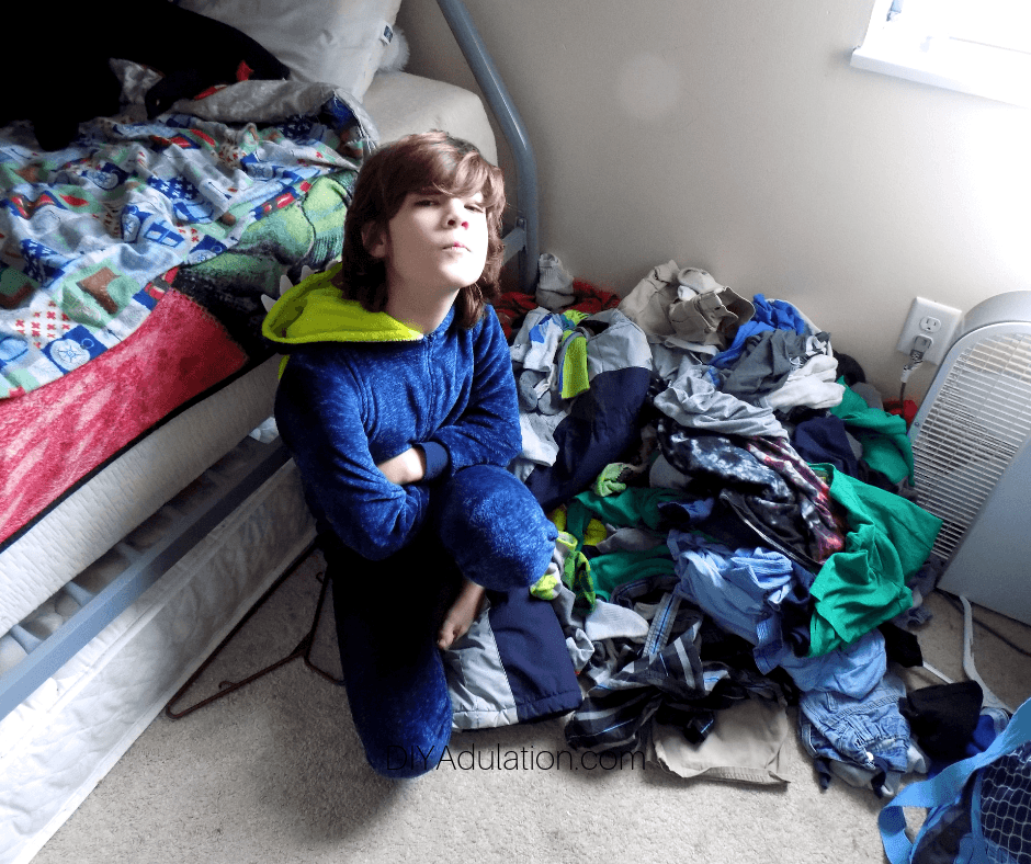 Boy Next to Pile of Clothes