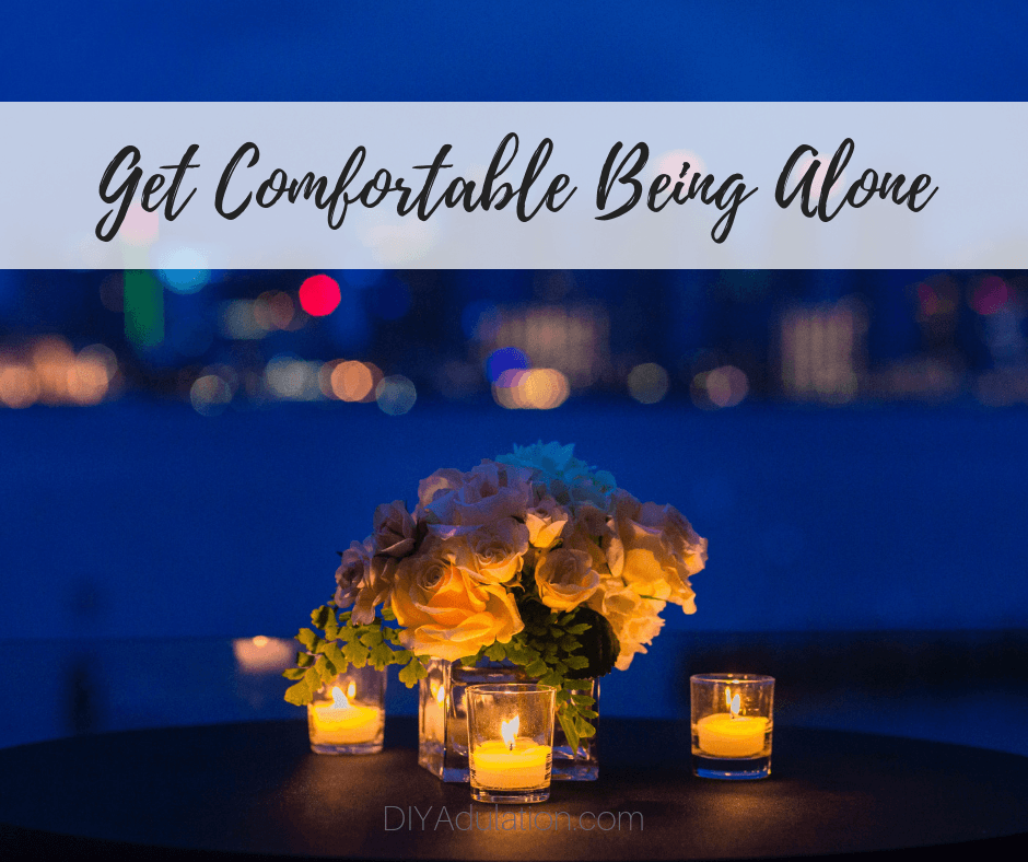 Candlelit table overlooking city skyline with text overlay - Get Comfortable Being Alone