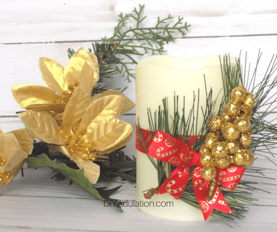 Christmas Candle next to Gold Flowers