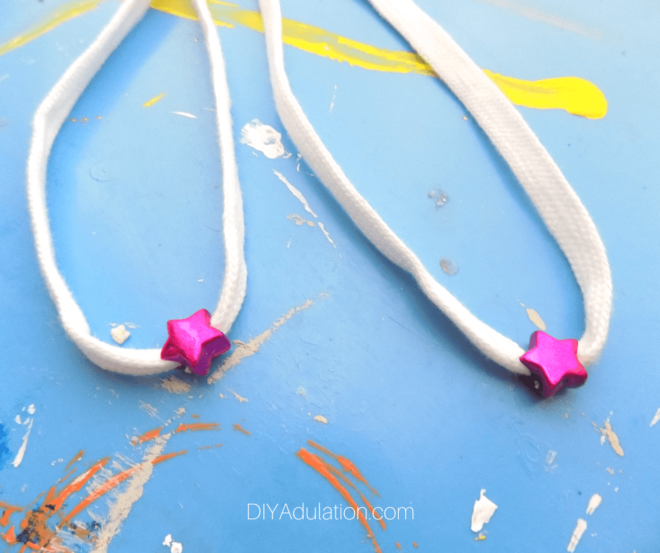 Close up of White Shoe Laces with pink star beads