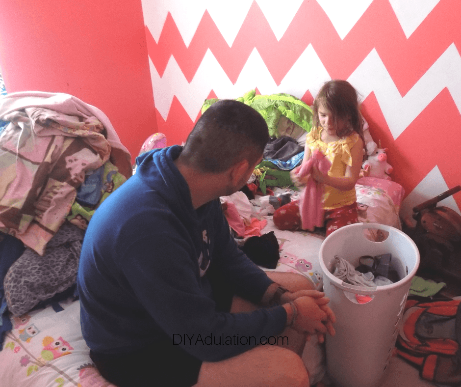 Dad and Daughter Sorting Through Clothes on Bed