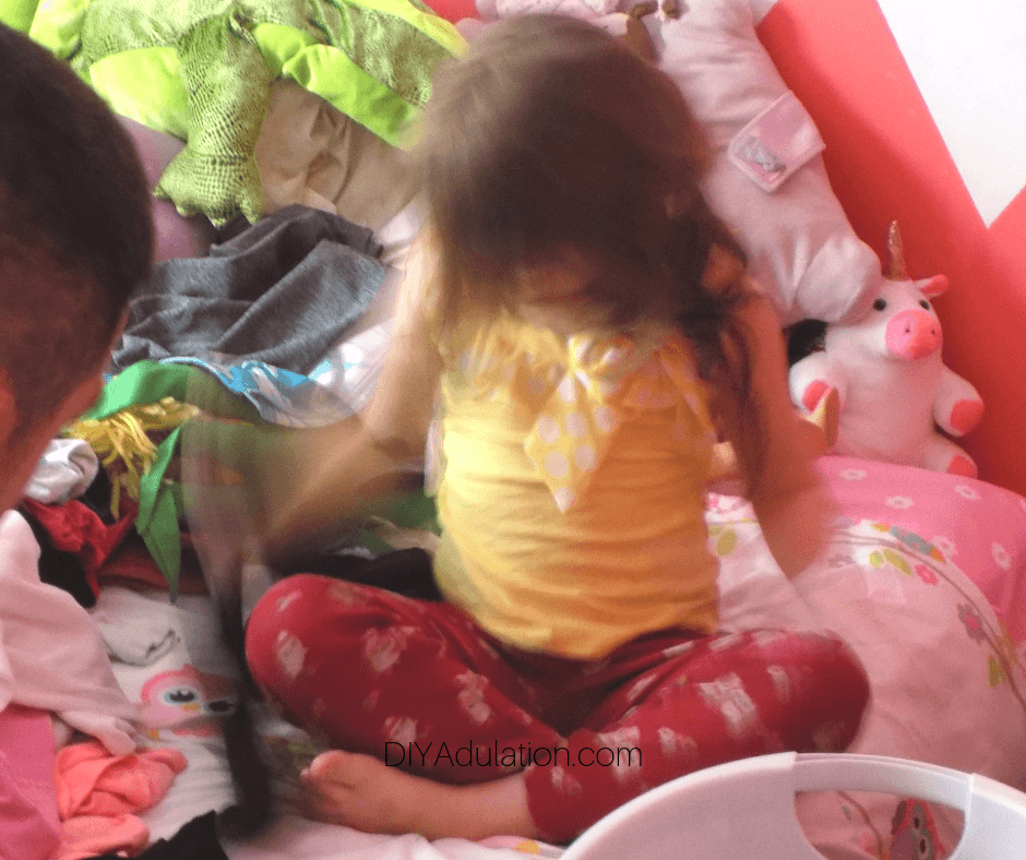 Daughter Sorting Through Clothes on Bed