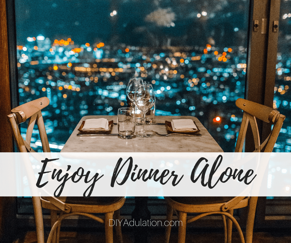Empty Table Overlooking City with text overlay - Enjoy Dinner Alone