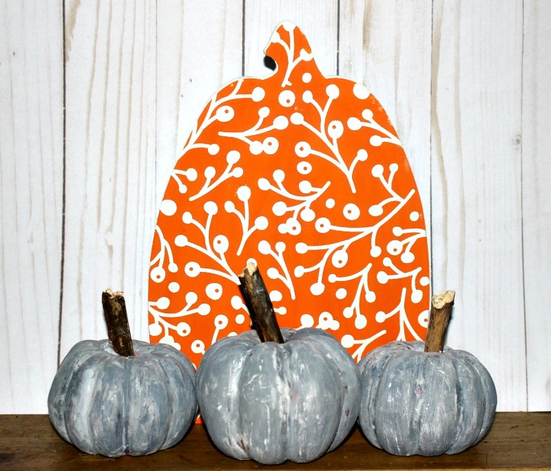 Faux Concrete Pumpkins in front of Orange Pumpkin Cutout
