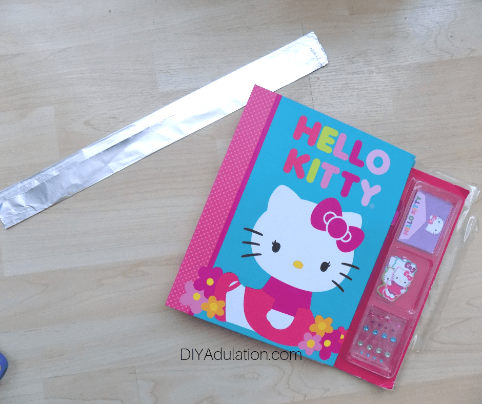Folded Piece of Foil next to Hello Kitty Book