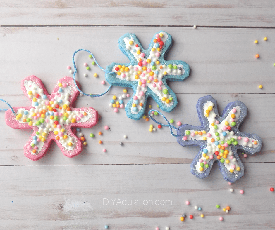 Glittery Snowflake Cookie Ornaments Next to Sprinkles