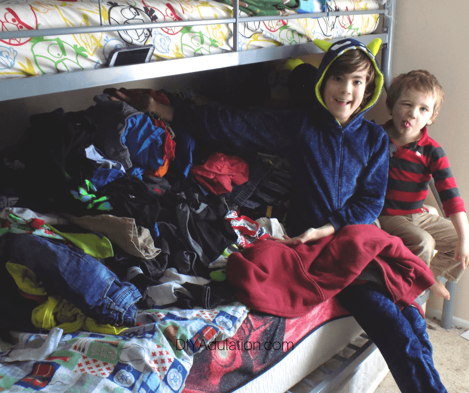 Kids Next to Clothes Piled on Bunk Beds