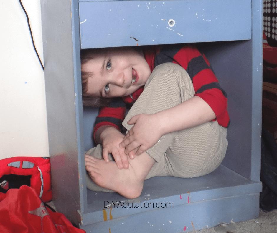 Little Boy Hiding In Night Stand