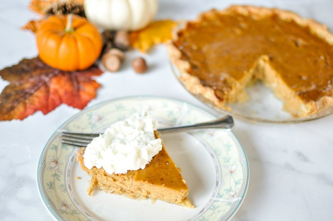 Slice of classic pumpkin pie next to whole pie