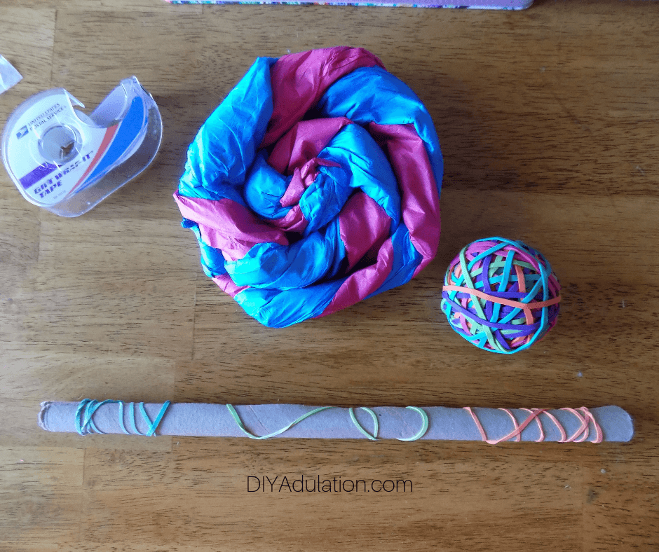 Rubber Band Wrapped Cardboard Tube Next to Blue and Pink Tissue Paper Swirl