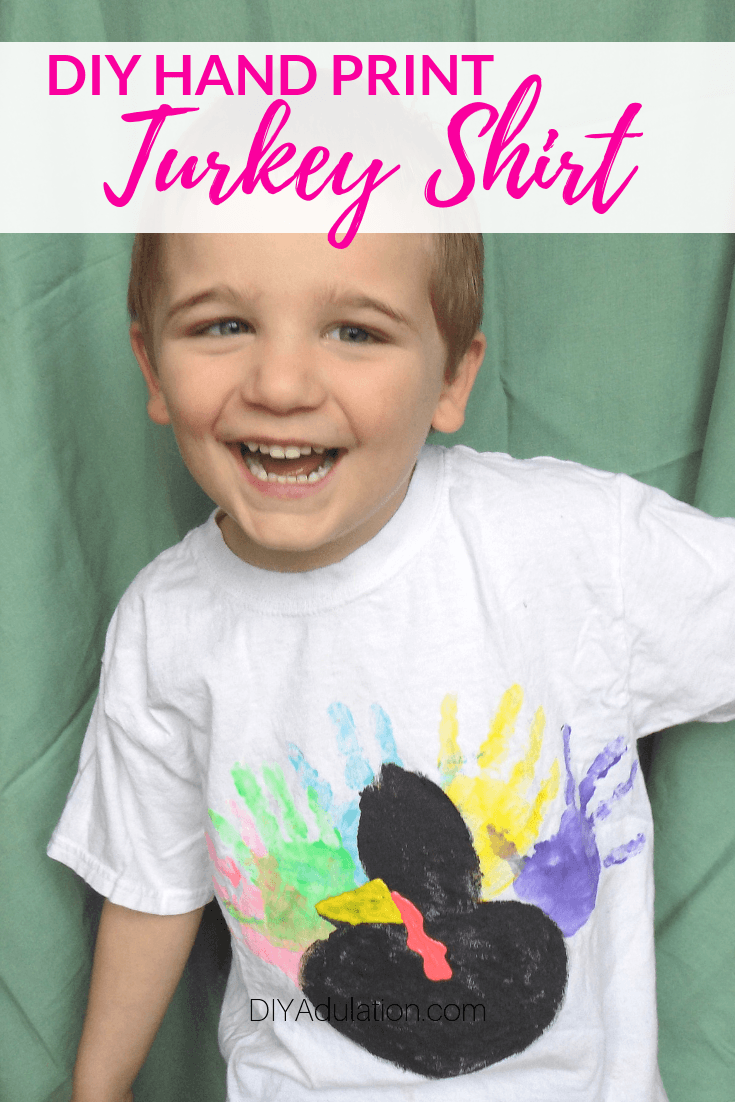 Smiling Boy Wearing a Hand Print Turkey Shirt with text overlay - DIY Hand Print Turkey Shirt