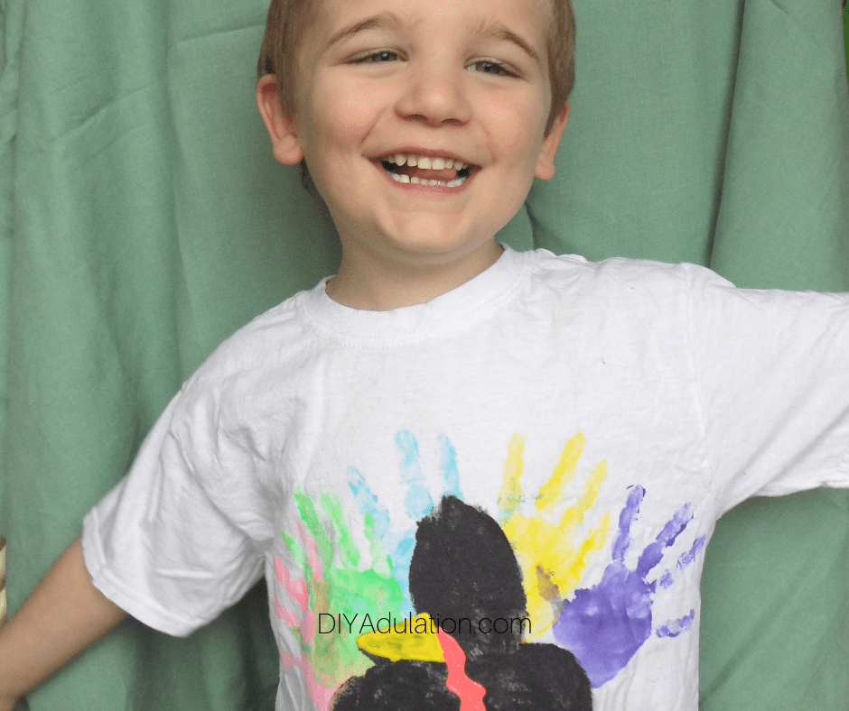 Smiling Boy in Hand Print Turkey Shirt with Arms Out