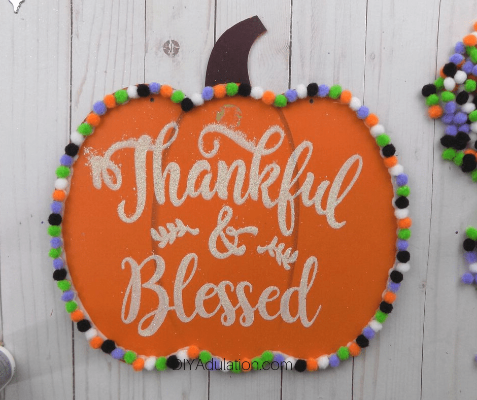 Thankful and Blessed Wooden Pumpkin Sign with Pompoms Around the Edge