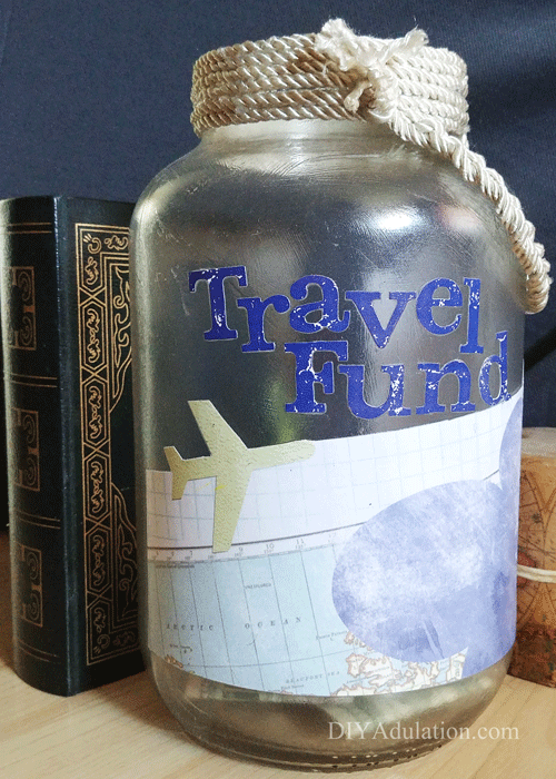 Travel Fund Jar next to Antique Book and Candle