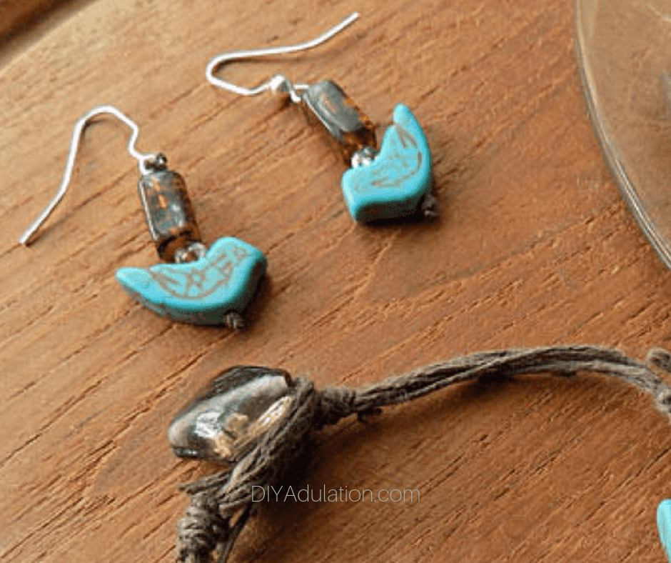Turquoise Bird Earrings on Wooden Background