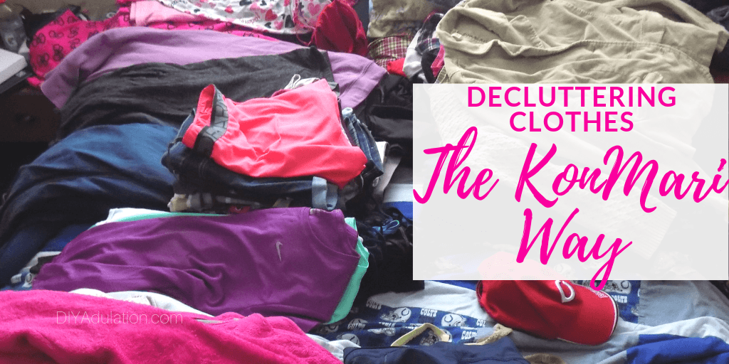 Stacked Piles of Clothing on Bed with text overlay - Decluttering Clothes the KonMari Way