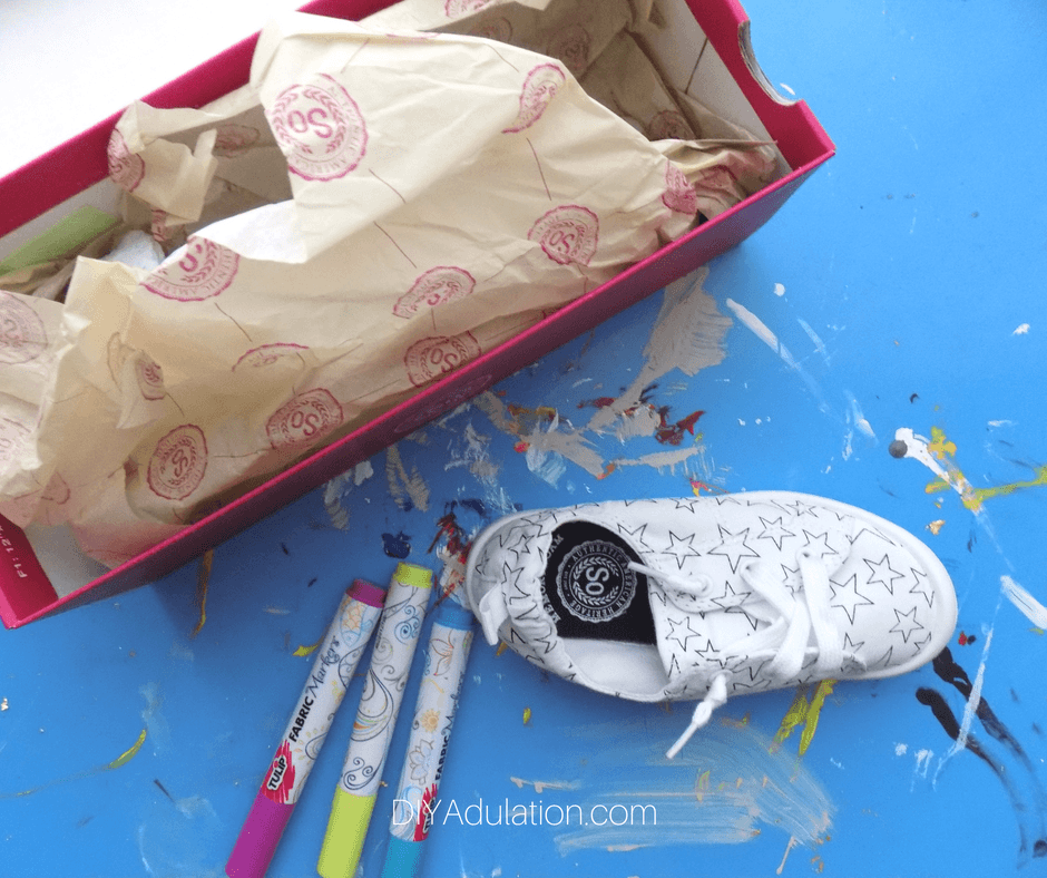 White Canvas Shoe next to Fabric Markers and a Shoe Box