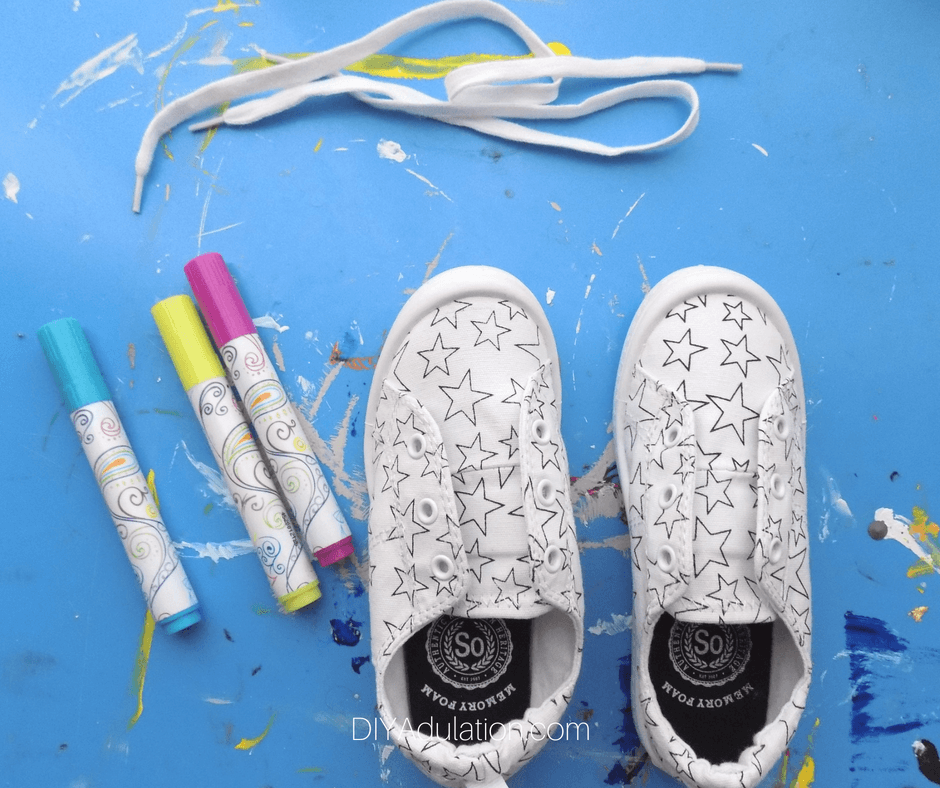 White Canvas Shoe with laces removed next to Fabric Markers