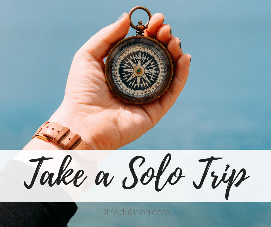 Woman Holding Compass with text overlay - Take a Solo Trip