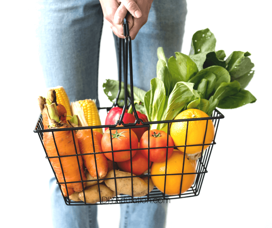Woman Holding Shopping Basket Full of Produce