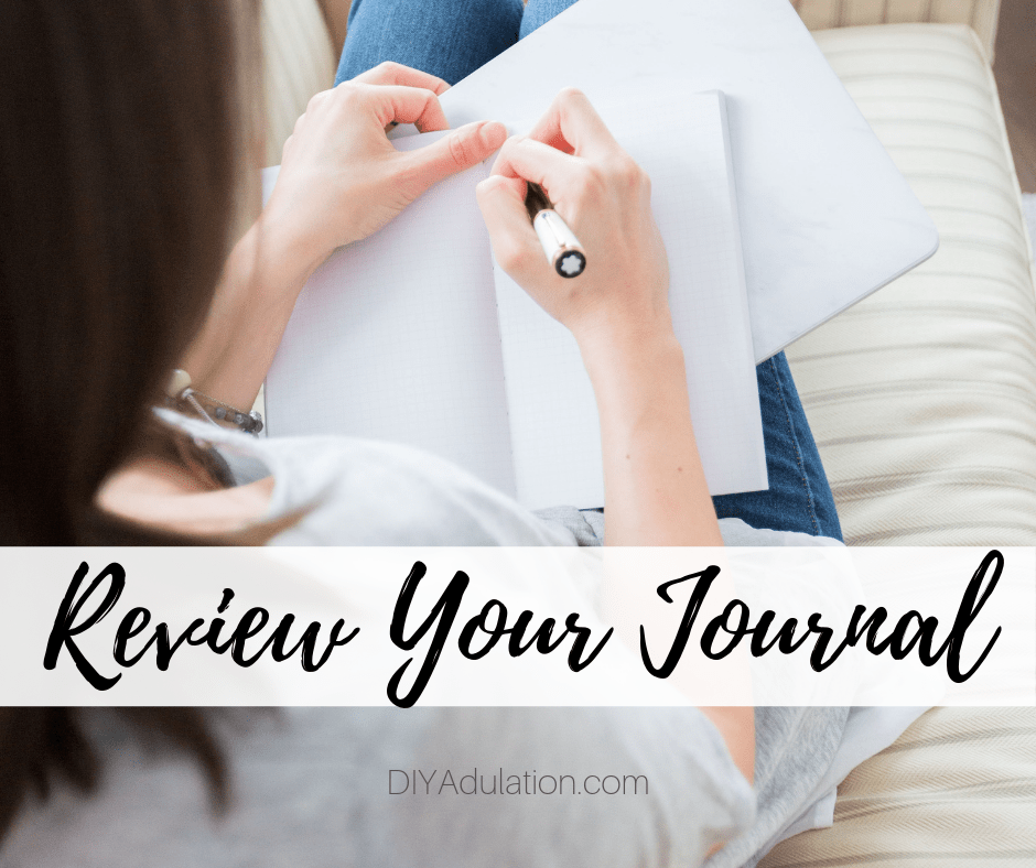 Woman Writing in Notebook with text overlay - Review Your Journal